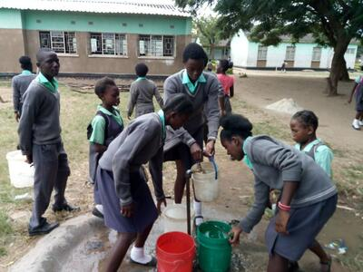 Matero East primary school students collecting water. Credit: Munich Advisors Group